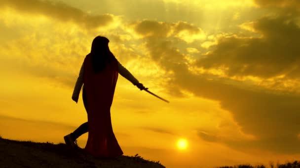 Egy vörös köpenyes szupernő karddal hadonászik egy hegyen a naplemente fényénél. Szabad nő, aki szuperhőst játszik. lány játszik római lenin fényes sugarak a nap ellen az ég
