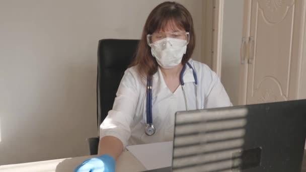Ärztin in weißem Kittel und Schutzbrille am Laptop, Online-Beratung und Konferenz. Doktor kommuniziert mit einem Klienten mittels virtuellem Chat. Telemedizin, medizinisches Fernversorgungskonzept.