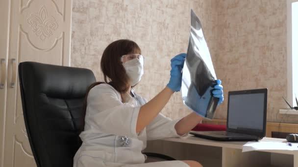 Eine Ärztin in einem Büro untersucht eine Röntgenaufnahme einer Patientin im Krankenhaus. Arzt arbeitet im Krankenhausbüro mit Laptop. Medizinische Versorgung und Gesundheitskonzept. Coronovirus-Pandemie, Lungenentzündung COVID-19