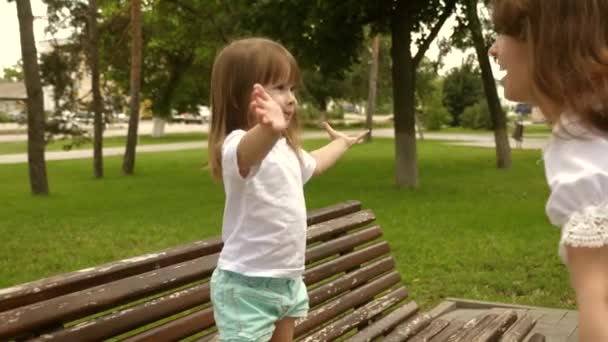 little daughter pulls her hands to her mother in park on a bench. Mom hugs happy healthy baby. Beautiful mother and her baby are playing in park. Happy Mothers Day Joy. concept of childhood.