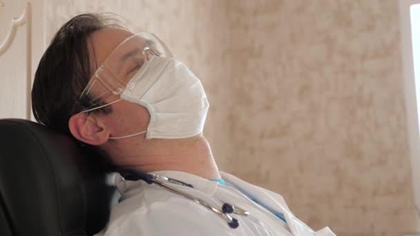 Müder Arzt mit medizinischer Schutzmaske und Brille ruht sich in der Praxis aus. Der Mediziner döste auf einem Stuhl in einem Krankenhaus. Sanitäter schloss Augen vor Müdigkeit und Überlastung