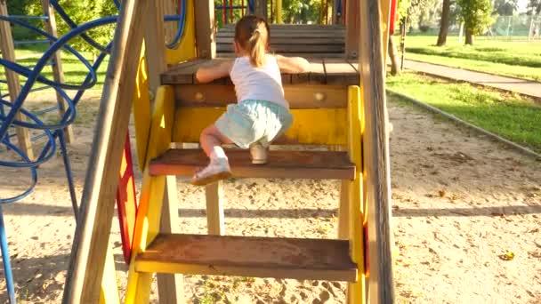 dítě stoupá po schodech až k dětským skluzavkám. matka a dítě si hrají na hřišti. Šťastné dětství. Šťastné dětství a rodinný koncept. malé dítě se směje a užívá si hřiště v parku