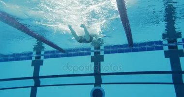 Professional female swimmer swimming in pool