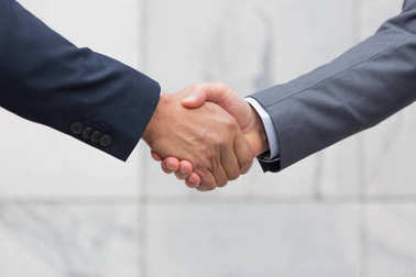 Closeup of Businessmen wearing suits shaking hands on meeting, standing in modern office