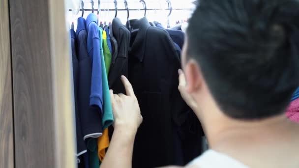 Muž vybírá oblečení doma za slunečného rána