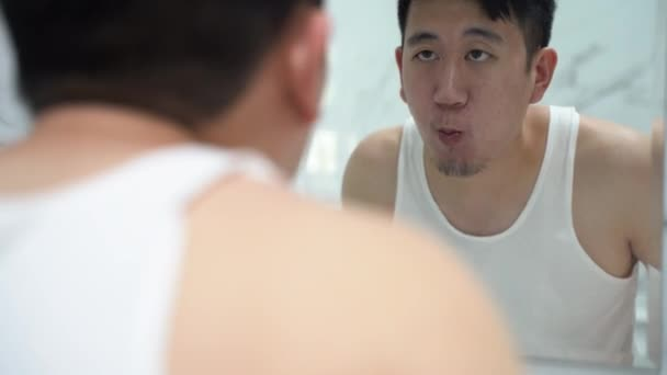 Asian man gargling with mouthwash in toilet