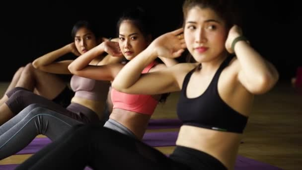 Ázsiai nőkből és férfiakból álló csoport, akik hasi gyakorlatokat végeznek jóga matracokon aerobik órán. Fiatal sportos emberek csavarja test a padlón tornaterem stúdió.