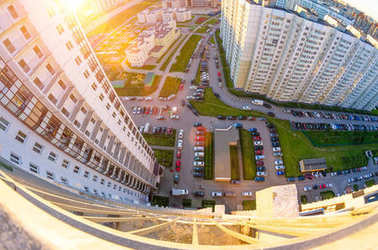 View from the height of the balcony to the sunset and the courtyard of the city landscape with cars and parking