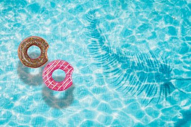 Blue swimming pool with rings floating