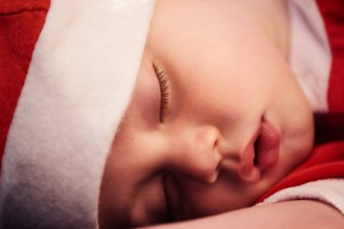 Close up of sleeping babys face in santa outfit