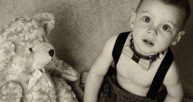 Baby boy sitting on soft blanket with a teddy bear