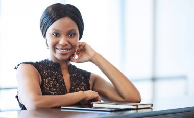 Sucessful black businesswoman looking into camera while seated at counter