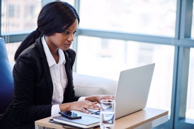 Black businesswoman working on her notebook in a business lounge