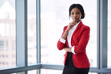 African businesswoman looking into camera confidently while wearing red blazer