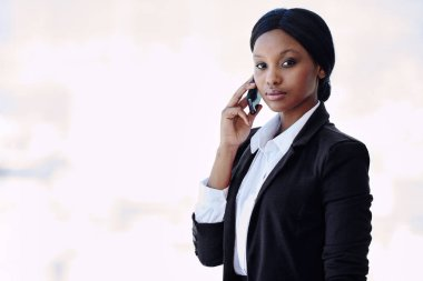 black businesswoman looking at camera while holding a cellphone