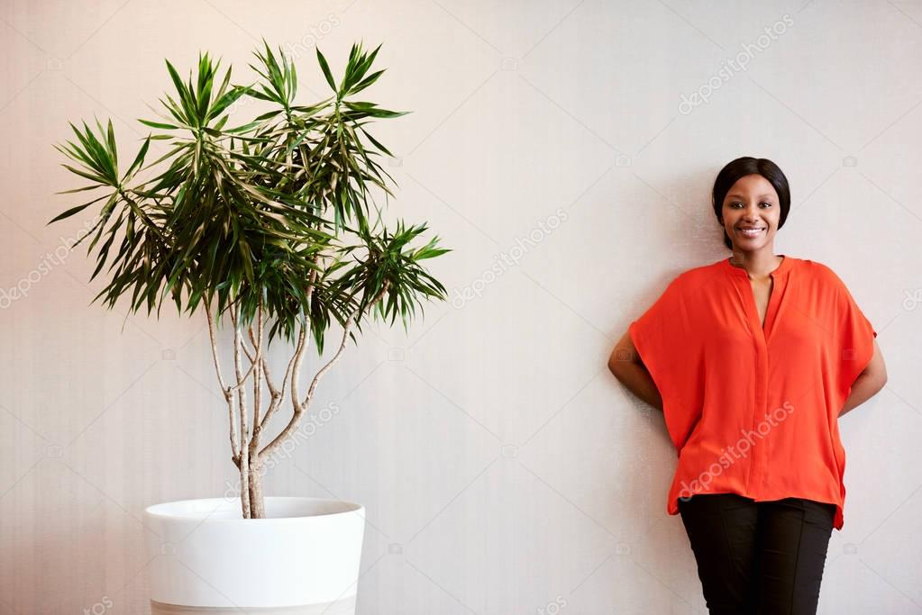 African businesswoman standing next to pot plant smiling at camera