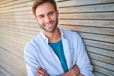 Attractive white guy smiling at camera leaning against wooden cladding