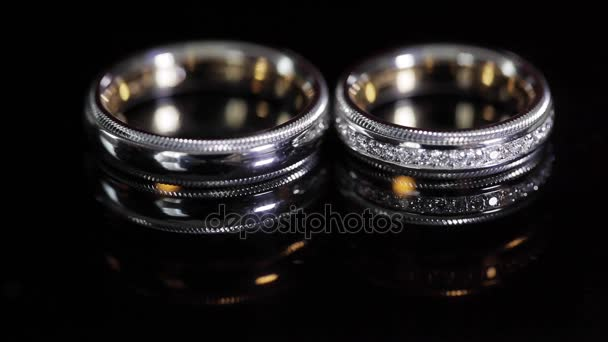 Wedding rings black background shining with light close up macro