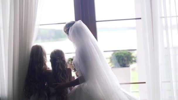 A menyasszony a kis koszorúslány az otthoni állni az ablak hát háttérvilágítás lassított. Hosszú fátyol szőke menyasszonya touch szép haj, a lánya vagy virág a lányok pillantást ablak vár vőlegény érkezik