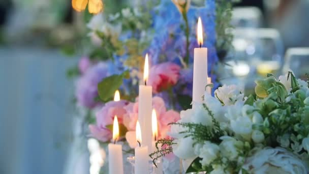 Candles and flowers close up colorful macro slow motion shallow depth of field. Table set for wedding reception banquet blur background glassware. Long wax candle flame light cozy romantic atmosphere