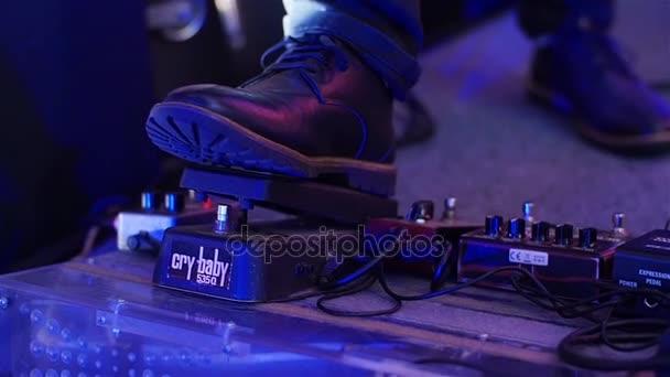 Pedalboardu stisknutí zblízka. Hudebník boy noha v botě šlapat na pedál účinky na živý koncert zpomaleně. Hráč na elektrickou kytaru muž stisknutí plochý pedalboard dělat hudební efekt reverb nebo zpoždění