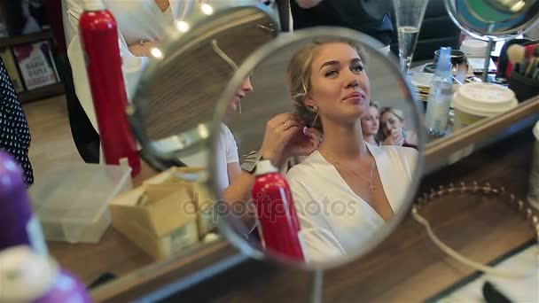hairstylist doing hair of woman in beauty salon mirror view close up happy young beautiful blonde bride model smiles being client of professional