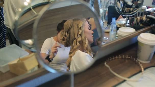 Vlasy kadeřnice využití sprej na vlasy žena zrcadlením zblízka rozostření pozadí. Mladá blondýna nevěsta modelu klient profesionální maskérka použití štětce k malování obočí v salonu krásy