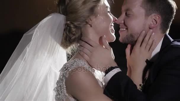 Nevěsta a ženich polibek usmíval se šťastný zblízka na černém pozadí. Okouzlující zamilovaný pár si spolu v lásce a čerstvě ženatý. Něha štěstí pospolitosti manželství svatební den koncept