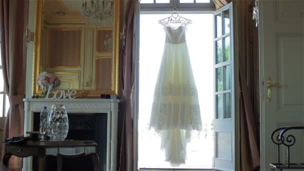 7e61f5198d Wedding dress hanging in doorway light waiting for bride tracking pan. Lace  decorated white bridal gown ...