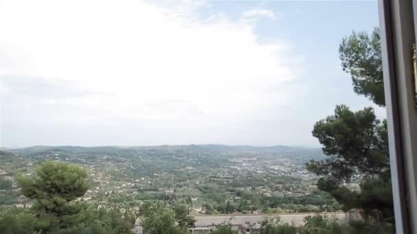 Otevřené okno na venkově zelené krajiny pohled kamery pohybující se uvnitř místnosti. Panoramatický výhled z velkých oken francouzské nebo italské vily na malebné venkovské údolí země zelených stromů a kopců v dálce