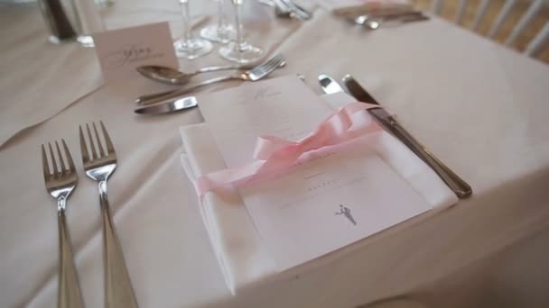 Dekorace na sváteční stůl uspořádány zblízka - menu a ubrousek s růžovou stuhou. Nádobí sada pro speciální příležitosti, svatbu, výročí přijetí nebo degustační menu v luxusní restauraci