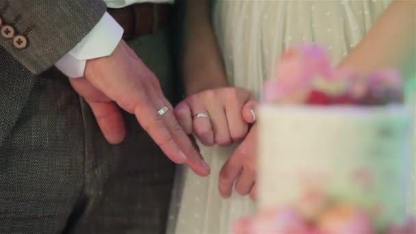 Novomanželé ukazující kroužků se zaměřením změny na krásné svatební dort zdobený přírodní růže kvete a bobule bez tváře zblízka stojan zaměření. Rautové uspořádání recepce a stravování