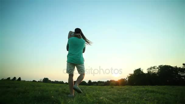 Young man spins and holds happy woman in arms twirling together at sunset backlit grass POV. Boyfriend rotates carrying smiling long hair girlfriend in sunny evening summer meadow. Love togetherness