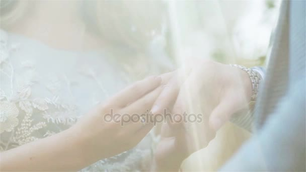Woman putting ring on mans finger close up through veil or sun light. Girlfriend proposing to girlfriend as gender equality concept. Exchanging wedding rings at ceremony in nature outdoors