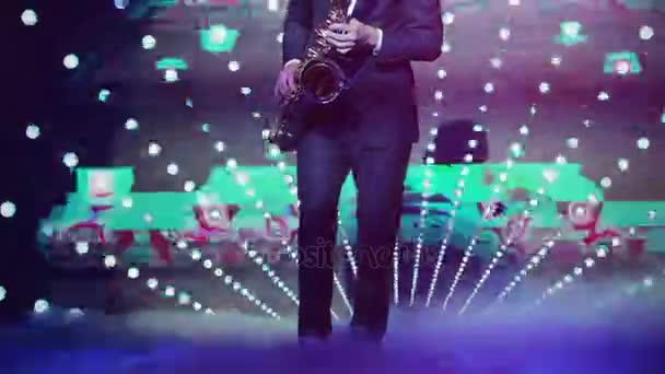 Játszik szaxofon éjszakai klubban nem felfelé közel kezek és a lábak csak. Szaxofonos játszik ő eszköze a Szilveszter párt strobing és glitching vj képernyő vetítés háttérrel