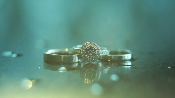 3 golden rings lightened up from top extreme close up. Engagement ring inlaid with blue crystal diamonds precious gem stones together with wedding rings macro shallow dof. Sun element details jewelry