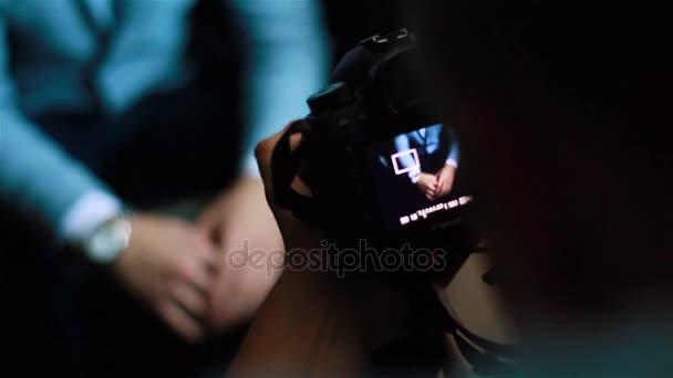 Zaměřuje na ruce fotoaparát zobrazení zblízka. Male ruce stavěcí objektiv pro vyfotit nebo natáčení video o foto kamery soudobé kinematografie. Kvalitní kameraman pracovní pohovor média zprávy