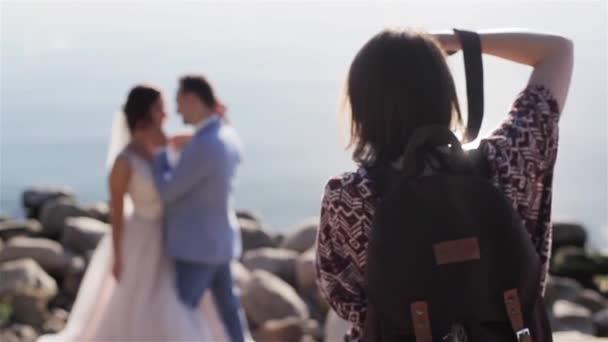Svatební fotograf pracuje dělat fotografie k nepoznání novomanželů nevěstu a ženicha páru pózuje venku na moři a podsvícení pozadí slunce. Svatební fotografie a lásce příběhy videoklipy