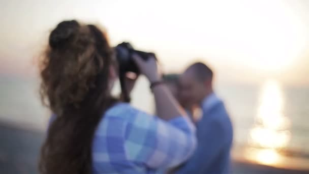 Photographer taking pictures of unrecognizable couple posing outdoors at sea and backlit sun background close up shallow depth of field. Nuptial wedding and love story photography