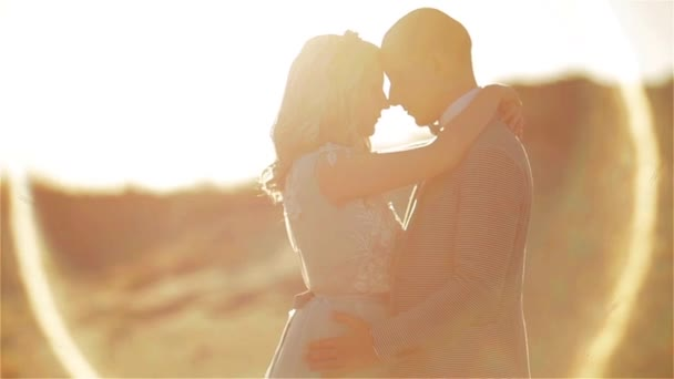 Mann und Frau posieren umarmt in morgendlicher Sandwüste in Großaufnahme von Köpfen und Beinen. Verliebte Paare stehen zusammen in der Aura der Sonne, die sich gegenseitig hält. Zweisamkeit Einheit Honigmond romantisches Konzept der Zuneigung