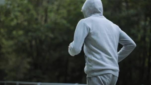 Mattina di uomo fare jogging nella foresta di montagna nelle vicinanze senza volto a rallentatore. Vista laterale posteriore maschio Pareggiatore eseguire su collina in felpa grigia con cappuccio e pantaloni allenamento. Stile di vita Wellness allenamento allaperto aria fresca