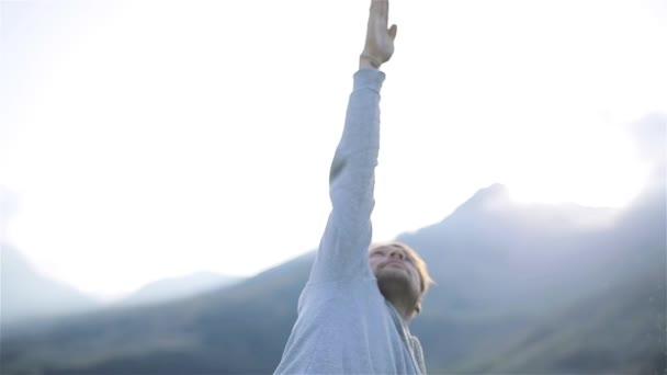 Jóga muž natahuje ruku do přírody hor blízko sluneční svit. Stojící v asana hledáte cvičení venku na slunné ráno nebo večer. Zdravého životního stylu trénink cvičit mužské sportovní koncept