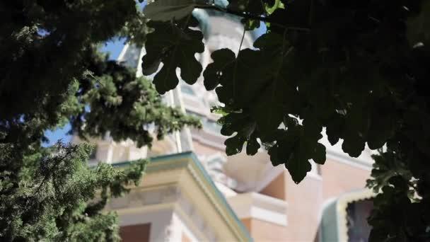Nizza, Frankreich - 27. Juli 2017: Nikolaus orthodoxe Kathedrale - Blick auf den Garten. Kuppeln mit goldenen Stil Kreuze und Engel an der Spitze als Baudenkmal Gebäude durch Baumblätter gesehen details