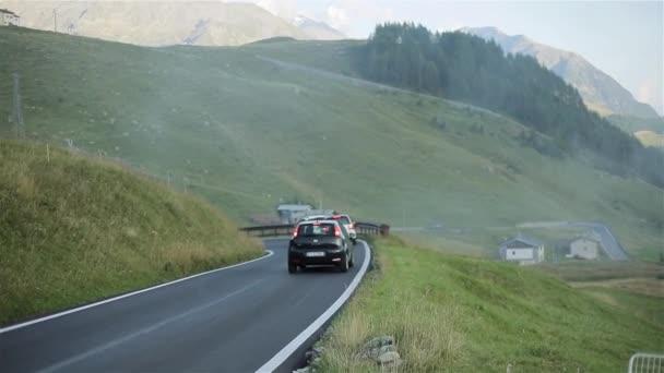 Autos bewegen Landschaft Bergstraße auf nebliger Morgen-Slow-Motion. Drei Autos bewegen Sie eins nach dem anderen langsam entlang der Serpentinenstraße Lane mit Schienen Sonnenaufgang Nebel Feld Wiese. Fahrzeuge fahren Reise Reise