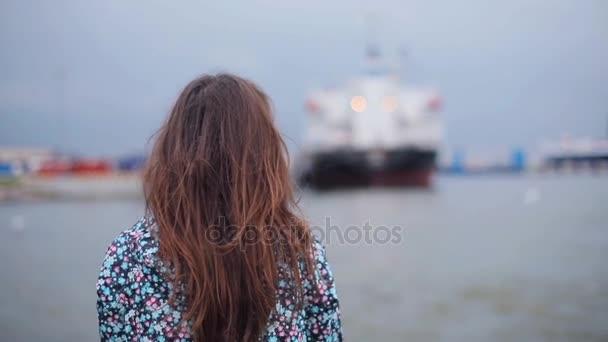 Dívka stojí zpět sleduje rackové a lodě v přístavu z výletní lodi odjezdu zblízka zpomaleně. Mladá žena cestování v přístavu vypadá strany těší pohled ptáků letící nad vodou