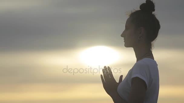 Žena zvýšit pálivých papriček Namaste pozdrav při západu slunce světlé pozadí boční pohled. Silueta ženy Jóga spojuje dlaně s tím šíření prsty pozdrav slunci v božské oblohy a vesmíru text vlevo