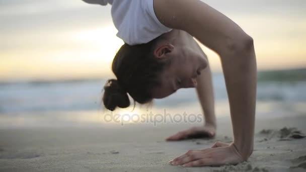 Žena stojí v póze nahoru luk kolo cvičit v západu slunce pláže, kterou rukou zblízka zpomaleně. Jóga asana gymnastika Chakrasana venku na písku oceánu. Provádění Urdva Dhanurasana s úsilím
