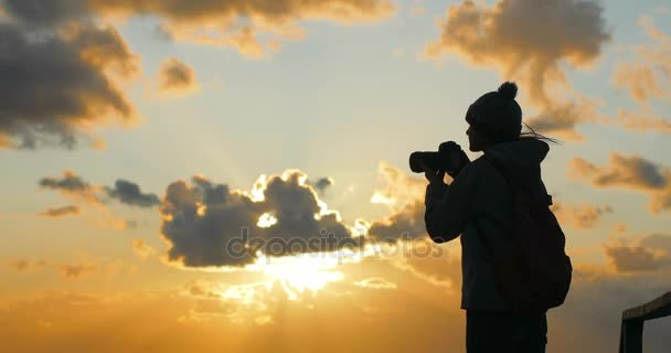 4 k Mädchen Fotograf Silhouette macht Fotos von göttlichen Sonnenuntergang Himmel mit Teleobjektiv Foto Kamera starken Wind am Abend auf dem Seeweg. Junge Frau im Hut professionell macht Fotos von Twilight-Wolken-Hintergrund