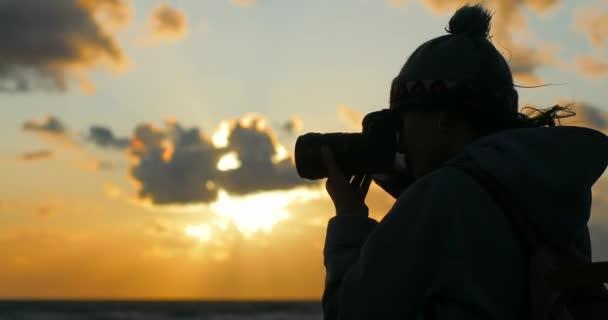 4 k junge Frau fotografieren Sonnenuntergang Meer Himmel wind am Abend schließen sich. Weibliche Silhouette nimmt Bilder halten professionelle Teleobjektiv Kamera Fokussierung Moment warten. Kamera-Ausrüstung bei schlechtem Wetter