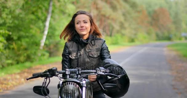 4k žena sedí na café racer vlastní motorce usmívající se dotýká vlasy podzimní příroda lesní cesta. Biker dívka na motocyklu pózuje začne motor ruce na řídítka připraven k jízdě sunny rozostřeného pozadí